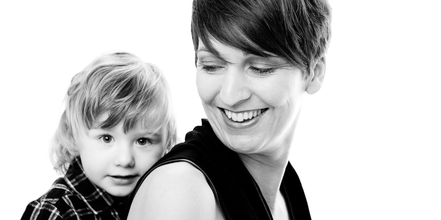 Family photography picture of Mum sitting side-on smiling with toddler boy seated behind her