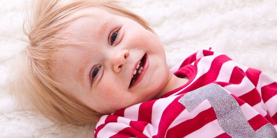 Family photography picture of cute blonde toddler smiling at the camera
