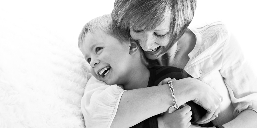 Mum smiles as she bear-hugs her young son